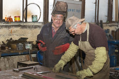 Metalworking shop workers work behind machines and apparatuses to create steel structures Royalty Free Stock Photography