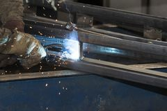 Metalworking shop workers work behind machines and apparatuses to create steel structures Stock Image