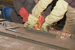 Metalworking shop workers work behind machines and apparatuses to create steel structures Stock Images