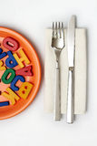 Metaphoric ''Food for thought''. Tableware set and alphabetic letters as the food for the mind stock images