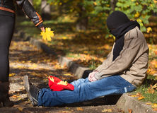 Metaphoric social photo with tramp man begging in autumnal park Royalty Free Stock Image