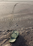 Long Way To Go. A metaphorical image of a lone flip flop with a long sand track ahead of it Stock Image