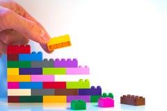 Metaphorischer Schuss der Spielzeugbacksteinmauer stockfoto