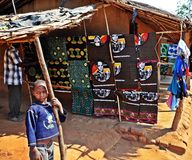Metarica Market - Niassa Mozambique. A young boy stands alongside a vendor's clothing stall in the Metarica market square Royalty Free Stock Photography