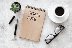 Metas de las palabras para 2018 que escribe en cuaderno cerca de los vidrios y de la taza de café en maqueta de piedra gris de la Imágenes de archivo libres de regalías