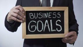 Metas de negocio escritas en la pizarra, hombre de negocios que lleva a cabo la muestra, estrategia almacen de video