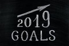 Metas del Año Nuevo 2019 con una tiza de levantamiento del texto de la flecha en una pizarra Pizarra escrita con metas del texto  imagen de archivo