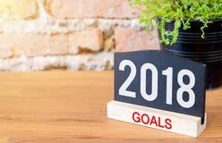 Metas del Año Nuevo 2018 en muestra de la pizarra y la planta verde en la madera t Imagen de archivo libre de regalías