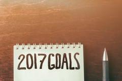2017 metas en el fondo y la pluma de papel del cuaderno en la tabla de madera, negocio Imágenes de archivo libres de regalías
