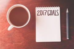 2017 metas enumeran con el cuaderno, taza de café en la tabla de madera Imagen de archivo