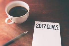 2017 metas enumeran con el cuaderno, taza de café en la tabla de madera Foto de archivo