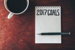 2017 metas enumeran con el cuaderno, taza de café en la tabla de madera Fotografía de archivo libre de regalías