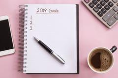 2019 metas enumeran con el cuaderno, taza de café encima en fondo rosado imágenes de archivo libres de regalías
