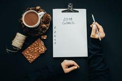 2018 metas enumeran con las manos de la mujer, lápiz, chocolate, cacao, cono Imagen de archivo