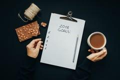 2018 metas enumeran con las manos de la mujer, lápiz, chocolate, cacao, cono Fotos de archivo libres de regalías