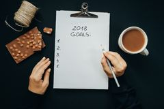 2018 metas enumeran con las manos de la mujer, lápiz, chocolate, cacao, cono Fotografía de archivo