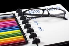 2018 metas mandan un SMS en el sketchbook blanco con la pluma del color y observan los vidrios Imágenes de archivo libres de regalías