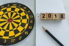 2018 metas y concepto de la blanco con número de bloques de madera y el dardo Imagen de archivo libre de regalías