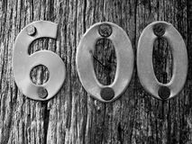 Metal Number 600 Nailed into Timber Post. Black & White Photo of Metal Number 600 nailed into a textured wooden electricity post stock photography