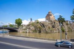Metekhi kyrka och hus på kanten av en klippa ovanför floden Royaltyfria Foton