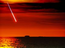 Meteor fall from space to ship on dark sea sunset sky Stock Image