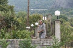 Meteora, Greece - September 19, 2018: Man working at backyards of village house stock image