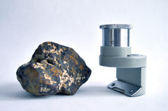 Meteorite and magnifying glass Stock Image