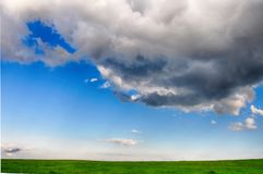 Meteorological image -  cumulus congestus cloud over a green meadow in the summer at daylight. Stock Images