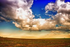 Clouds over the agriculture field in the summer at daylight. Horizon, relaxing mystique Royalty Free Stock Images