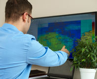 Meteorologist. Handsome male meteorologist working with touchscreen Stock Photos
