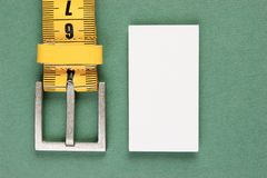 Meter belt slimming and blank business card. On the green background royalty free stock photography