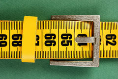Meter belt slimming. On the green background royalty free stock photo