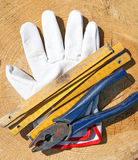 Meter, glove and pilers. On wooden background royalty free stock photos