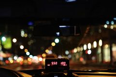 Meter of taxi cab driving through city Royalty Free Stock Image