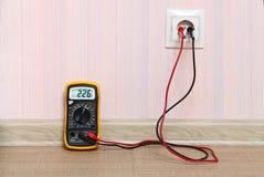 Metering socket voltage with digital multimeter. Royalty Free Stock Photo
