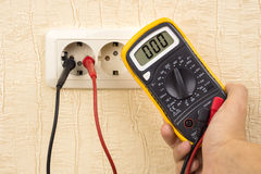 Metering voltage with digital multimeter. Metering socket voltage with digital multimeter Royalty Free Stock Image
