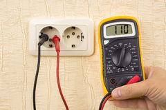 Metering voltage with digital multimeter Stock Photos