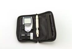 Metern för blodglukos, värdet för blodsocker mätas på en fingerpacke i svart fall på vit bakgrund Fotografering för Bildbyråer