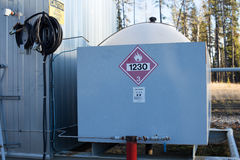 A methanol tank at natural gas wellhead facility. Red hazard caution sign Royalty Free Stock Photos