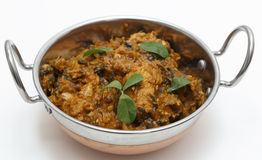 Methi chicken in a kadai. Methi murgh - chicken cooked with fresh fenugreek leaves - in a kadai, or karahi, traditional Indian wok, over white Royalty Free Stock Photo