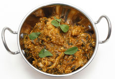 Methi chicken in a kadai. Methi murgh - chicken cooked with fresh fenugreek leaves - in a kadai, or karahi, traditional Indian wok, over white, garnished with Royalty Free Stock Photo