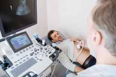 Methodical determined doctor scanning young mans organs. I am an expert. Committed mature professional examining patients stomach using an ultrasound technology stock photo