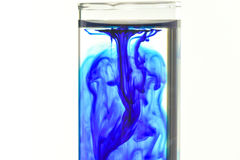 Methylene blue fall in water in glass tube stock photos