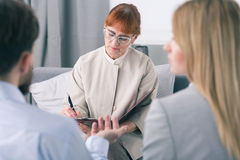 Meticulous listening to marital problems is her job. Female focused psychotherapist makes notes during couple therapy Stock Photos