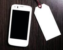Metka z telefonem komórkowym na drewnianym tle pusta etykiety Obraz Royalty Free
