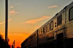 Metra火车移动入日落在一晚冬天结束时 免版税库存图片