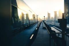 Metra i metra pociąg w mieście Futurystyczny nowożytny transport publiczny Dubaj koleje przy zmierzchem z drapacz chmur budynkami fotografia stock