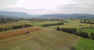 Metragem aérea da colheita de milho com liga e do trator em um fieldon um campo filme