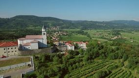 Metragem aérea da cruz antiga de Vipava da vila acima do vale do vipava com a igreja da cruz de Santa filme