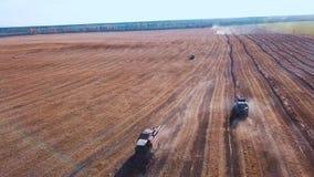 Metragem aérea de um trator moderno que ara o campo seco, preparando a terra para semear semeação no fim da estação Planta filme